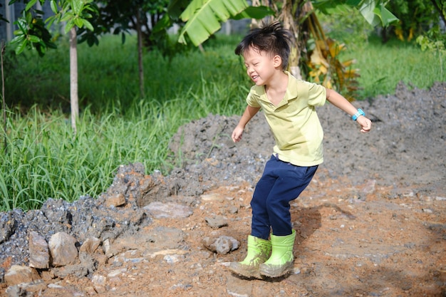 Nettes glückliches kleines asiatisches kindergartenkind, das grüne stiefel trägt, springen in schlammige pfützen auf natur