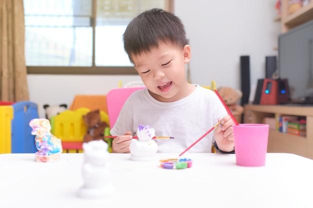 Nettes glückliches kleines asiatisches kleinkindjungenkind, das farbe auf diy gipsmalerei spielzeug malt