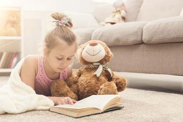 Nettes glückliches kleines beiläufiges mädchen, das teddybären und lesebuch umarmt, eingewickelt in weiße decke. hübsches kind zu hause, das mit ihrem lieblingsspielzeug auf dem boden neben dem sofa liegt, platz kopieren