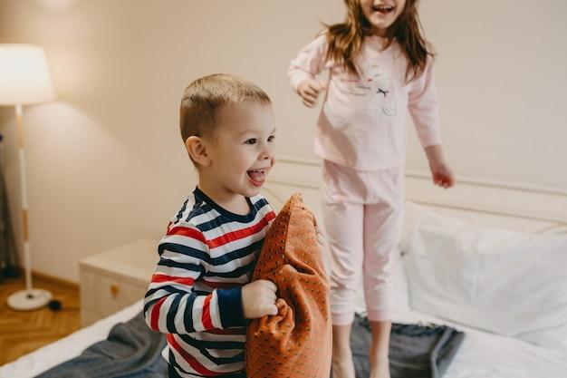 Nettes glückliches kleines kind, das ein kissen auf dem bett hält, während seine schwester am morgen springt.
