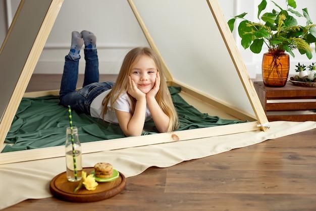 Nettes glückliches kleines mädchen, das in einem zelt aufwirft