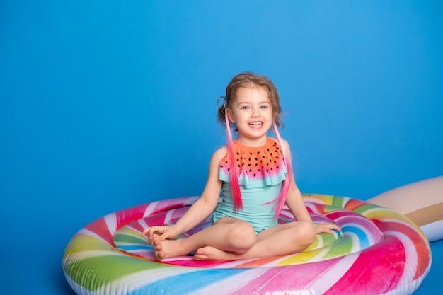 Nettes glückliches kleines mädchen im badeanzug lächelnd sitzend auf bunter aufblasbarer matratze.