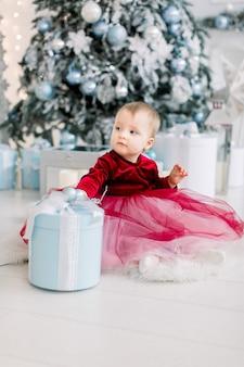 Nettes glückliches kleines mädchen im roten kleid spielt mit weihnachtskastengeschenk und sitzt auf dem boden