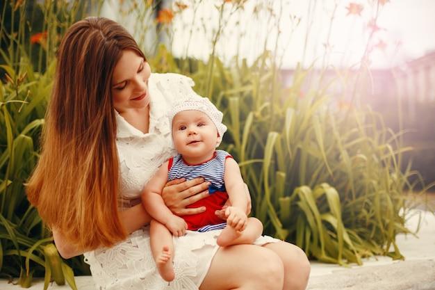 Nettes glückliches kleinkind, das auf liebevollen mutter `s knien sitzt