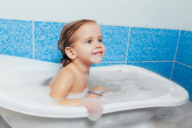 Nettes glückliches kleinkindbaby des spaßes, welches das bad spielt mit schaumblasen nimmt.