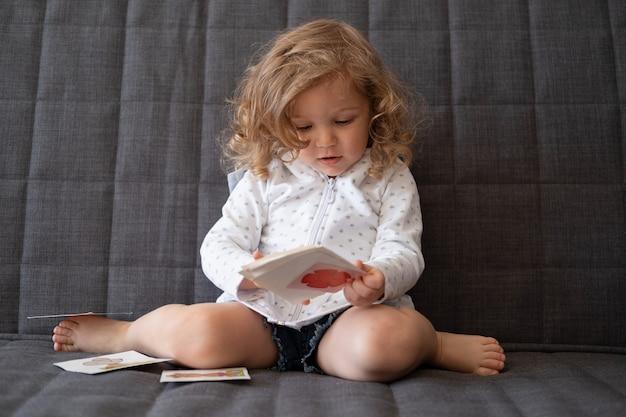 Nettes glückliches kleinkindmädchen spielen mit frühen entwicklungskarten, die auf couch sitzen. kinder farbige karteikarten. spielzeug für kleine kinder.