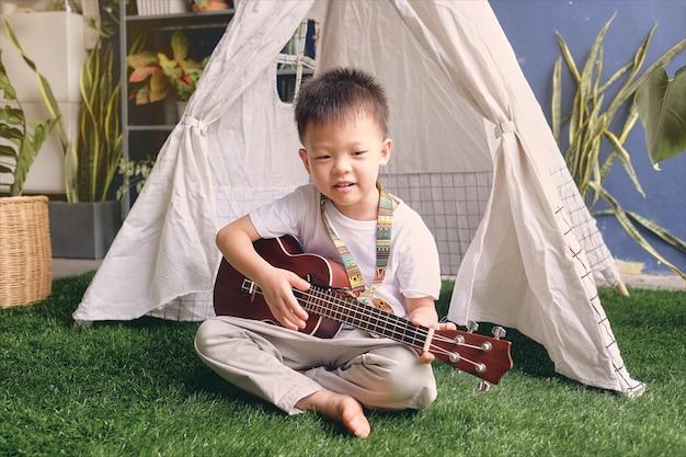 Nettes glückliches lächelndes kleines asiatisches kindergartenjungenkind, das spaß hat, hawaiianische gitarre oder ukulele zu spielen