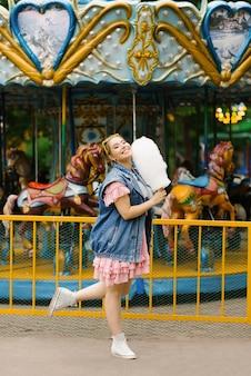Nettes glückliches mädchen, das zuckerwatte hält und im vergnügungspark im sommer lächelt