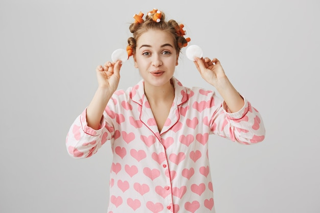 Nettes glückliches mädchen in nachtwäsche und lockenwicklern wischen make-up mit wattepads ab