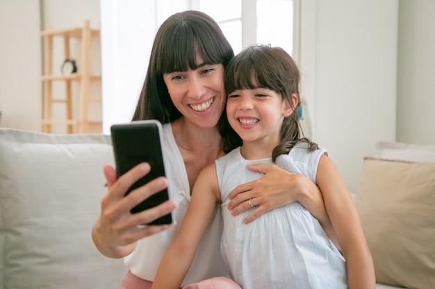 Nettes glückliches mädchen und ihre mutter, die telefon für videoanruf verwenden, während sie zusammen auf sofa zu hause sitzen