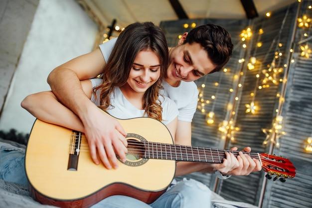 Nettes glückliches paar, das gitarre spielt