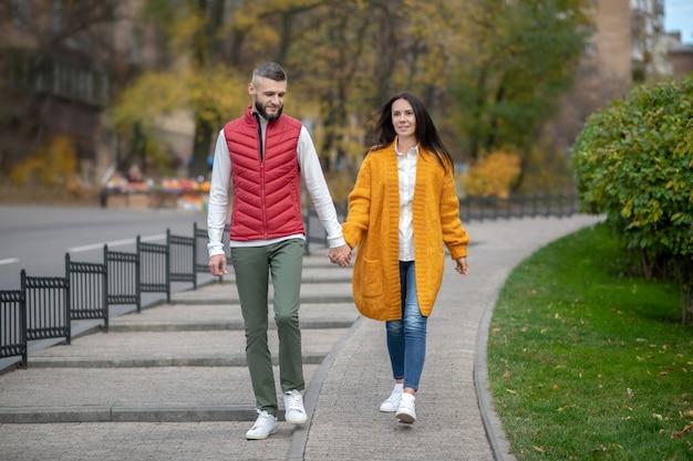 Nettes glückliches paar, das ihre hände zusammenhält, während es die straße entlang geht