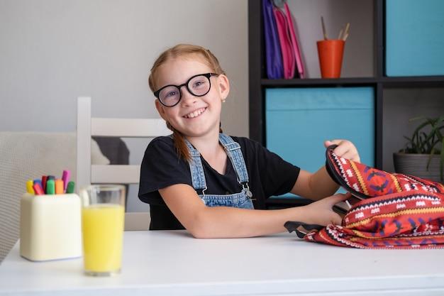 Nettes glückliches rothaariges mädchen in brillen, die rucksack packen und sich auf die schule vorbereiten. zurück zum schulkonzept.