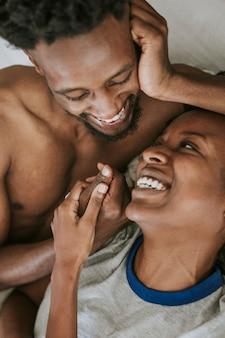 Nettes glückliches schwarzes paar, das im bett spielt