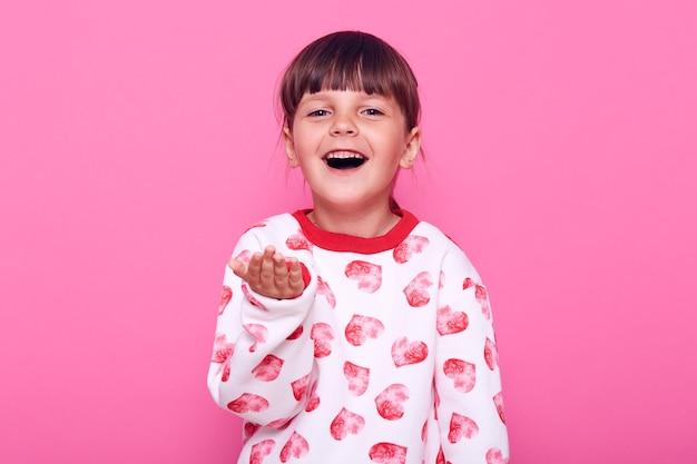 Nettes glückliches vorschulkindmädchen, das lässiges sweatshirt mit herzen trägt und handfläche ausbreitet, befriedigten ausdruck, gute laune, lokalisiert über rosa wand.