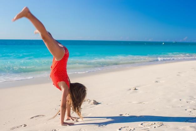 Nettes gymnastisches kleines mädchen, das ihre übungen auf tropischem strand tut