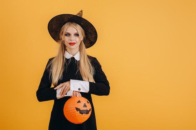 Nettes halloween-mädchen, das eine gemalte orange schrift auf einem orangefarbenen wandhintergrund hält. hochwertiges foto