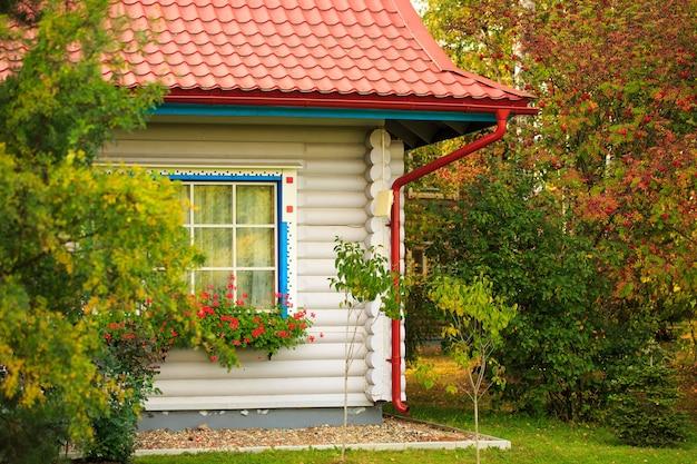 Nettes haus mit rotem dach im wald, umgeben von bäumen schönen sonnigen herbsttag ein ferienhaus aus...