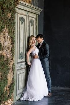 Nettes hochzeitspaar im inneren eines klassischen studios dekoriert. sie küssen und umarmen sich.