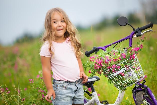 Nettes hübsches kleines mädchen auf der natur mit fahrrad und dem korb voller blumen. überraschtes mädchen, das fahrrad fährt