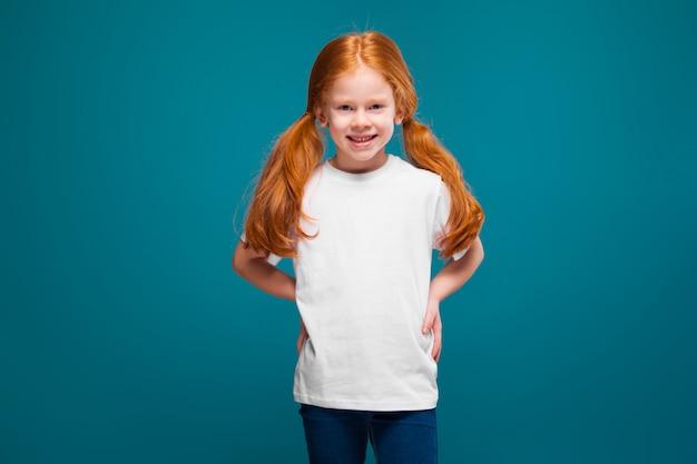 Nettes, hübsches, kleines mädchen im t-shirt mit dem langen roten haar
