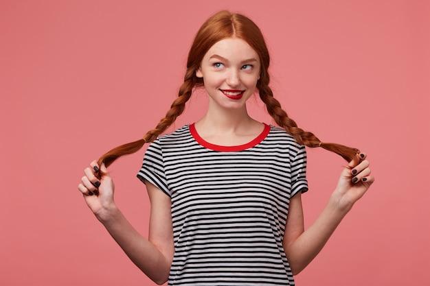 Nettes hübsches rothaariges mädchen mit roten lippen, die zwei zöpfe in den händen halten, gekleidet in abgestreiftem t-shirt, flirtend spielerisch betrachtend das linke obere eckplotterabenteuer isoliert