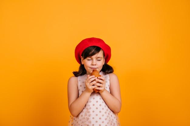 Nettes hungriges kind, das croissant isst. dunkelhaariges kleines mädchen isoliert auf gelber wand.