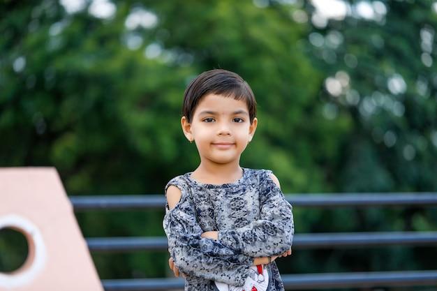 Nettes indisches kind, das auf haus steht