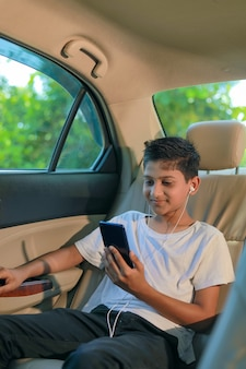 Nettes indisches kind, das im auto sitzt und smartphone und kopfhörer gadget verwendet