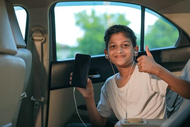 Nettes indisches kind, das smartphone mit schlägen oben im autofenster zeigt