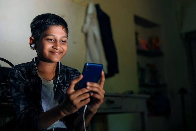 Nettes indisches kind, das smartphone und kopfhörer gadget verwendet