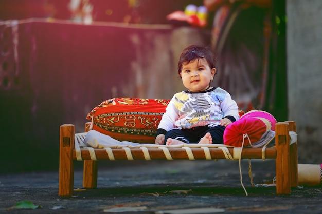 Nettes indisches kleines kind, das auf hölzernem bett spielt