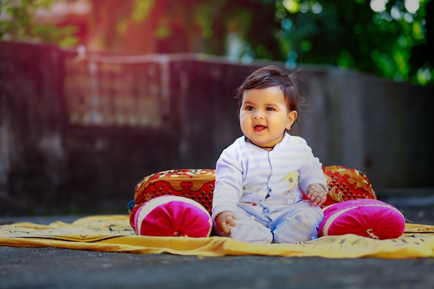 Nettes indisches kleines kind, das vor haus lächelt und spielt