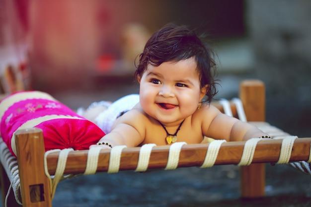 Nettes indisches kleines kind lächeln und spielen auf hölzernem bett