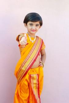 Nettes indisches kleines mädchen im traditionellen kleid und zeigt daumen hoch