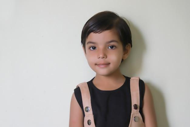 Nettes indisches mädchenkind, das ausdruck auf weiß zeigt