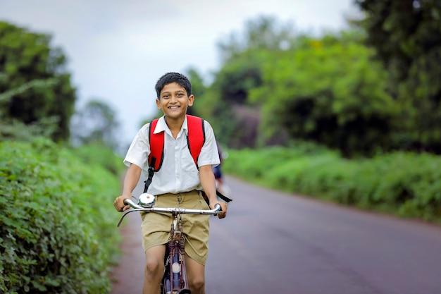 Nettes indisches schulkind, das auf zyklus zur schule geht