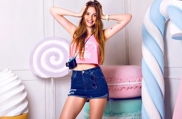 Nettes innenporträt der jungen schönen frau nahe riesigen bunten requisitenbonbons. lächelnd, hand nahe gesicht halten. mädchen, das rosa sommerunterhemd und blaue shorts trägt