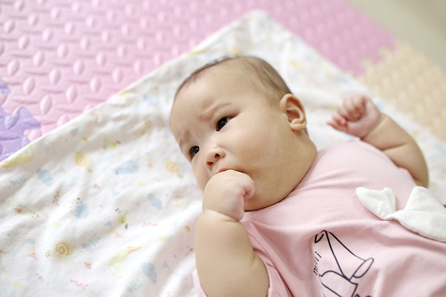 Nettes intelligentes asiatisches neugeborenes baby, das zu hause mit teddybärkaninchenspielzeug auf rosa weichem bett schläft.