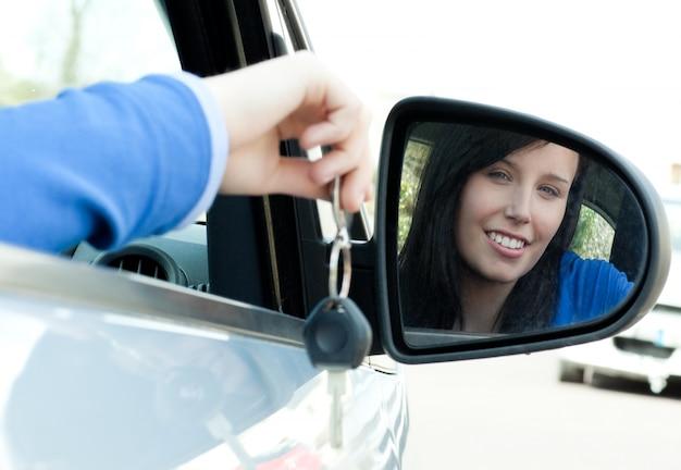 Nettes jugendlich mädchen, das in ihrem auto hält schlüssel sitzt