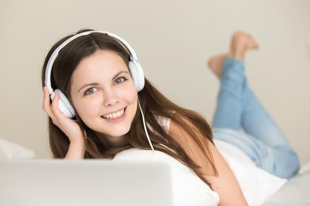 Nettes jugendlich mädchen, das online hörende neue musik genießt