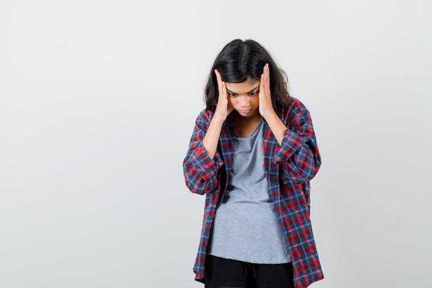 Nettes jugendlich mädchen in kariertem hemd, das den kopf mit den händen umklammert, nach unten schaut und deprimiert aussieht, vorderansicht.