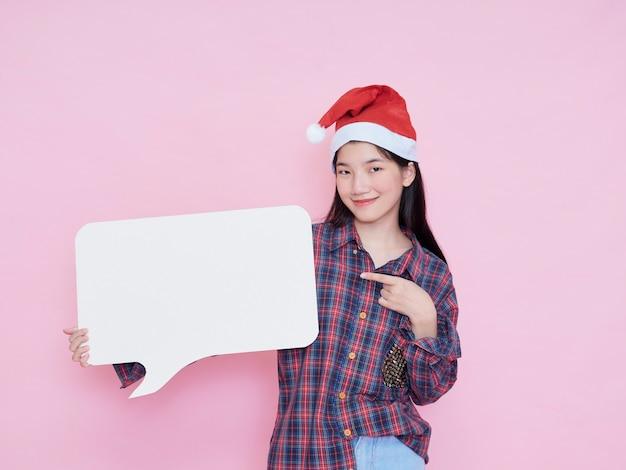 Nettes jugendliches mädchen in der weihnachtsmütze, die finger auf leerem plakat auf rosa hintergrund zeigt.