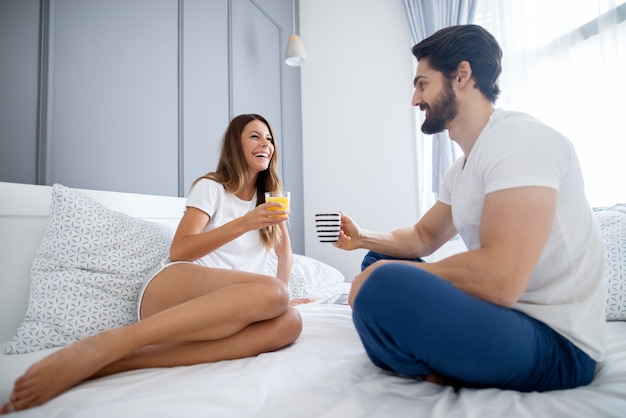 Nettes jugendliches mädchen lächelnd, während auf dem bett mit einem glas saft in unterwäsche mit einem jungen mann haltend becher mit kaffee sitzt.