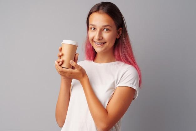Nettes jugendlichmädchen, das einen tasse kaffee anhält