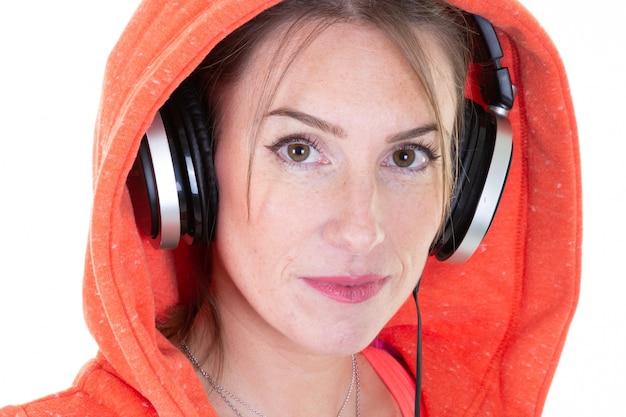 Nettes junges blondinemädchen im sportlichen mädchen des orange strickjackenleute-lebensstilkonzeptes hören musik mit kopfhörern