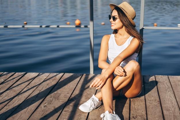 Nettes junges brunettemädchen, das auf dem pier nahe see sich entspannt.
