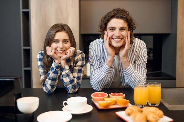 Nettes junges ehepaar, das zusammen ihr frühstück genießt.