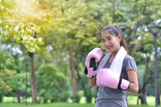Nettes junges eignungsmädchen in den rosa boxhandschuhen im park, lächelnd mit kamera