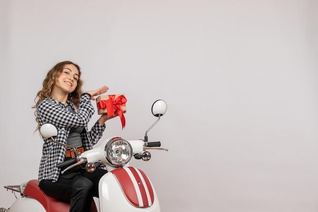 Nettes junges mädchen auf moped, das geschenk auf grau hält
